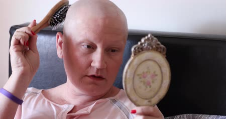 bipolar disorder : Mentally ill woman with bald head looking at the mirror and brushing her hair