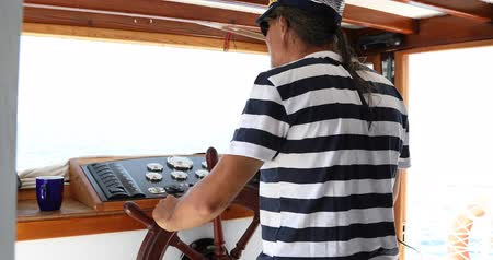motoring : Male skipper hands on a steering wheel of a boat motoring in mediterranean Sea