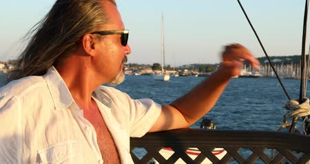 voyager : Handsome, happy man with long hair sitting on a yacht deck and listening to music, singing. Relaxing under the summer sun at summer holiday. Marine, people, summer, vacation, travel,nature, tourism concept. Stock Footage