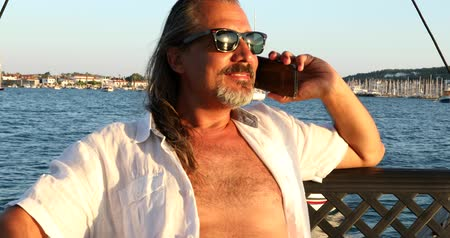 lux : Portrait of the middle aged businessman on luxury sailboat relaxing and  talking on the phone at the summer vacation.