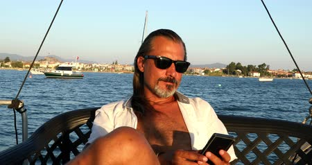 предназначенный только для мужчин : Handsome, relaxed businessman sitting on yacht deck and checking his phone. Enjoying summer vacation. Marine, people, summer, vacation, travel,nature, tourism concept. Стоковые видеозаписи