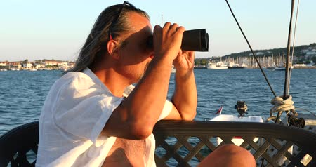 curioso : Portrait of a middle aged businessman sits on sailing yacht looks through binoculars.  Marine, people, summer, vacation, travel,nature, tourism concept.