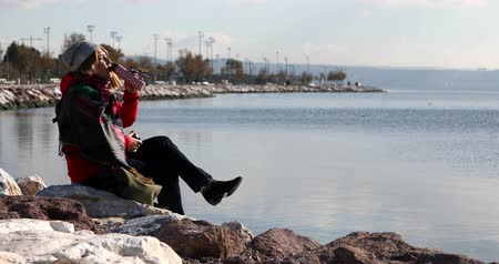 contemplative : Middle age woman with winter clothing sitting on the shore line and relaxing at the outdoor