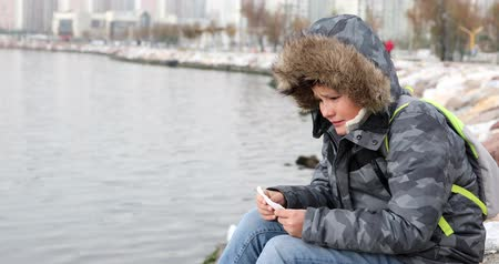 coughing : Sick preteen boy sneezing during cold day wearing warm clothes outdoor