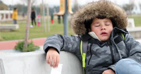 irritação : Sick child sneezing during cold day wearing warm clothes outdoor