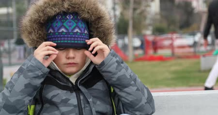 Sick child sneezing during cold day wearing warm clothes outdoor