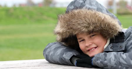 Happy little boy with winter clothes smiling at camera in park at winter time