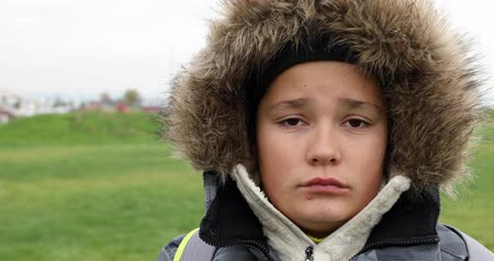znuděný : Portrait of a unhappy teen with winter clothes looking at camera at winter city park