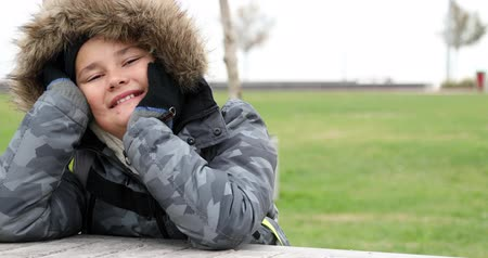 posou : Happy little boy with winter clothes smiling at camera in park at winter time