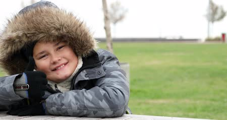 Portrait of happy little boy with winter clothes smiling at camera and  gesturing a thumbs up sign in park at winter time Dostupné videozáznamy