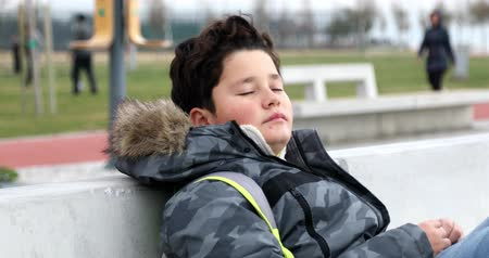 Portrait of a caucasian young boy with winter clothes sitting on a park bench alone
