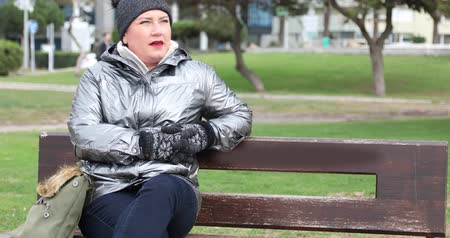 Woman sitting on a bench in winter coat looking at camera and smiling