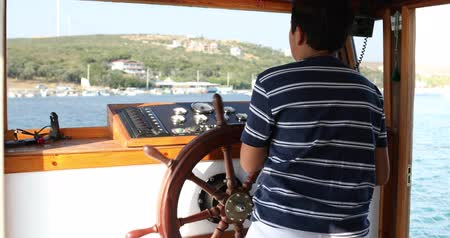 motoring : Young male skipper hands on a steering wheel of a boat motoring in mediterranean Sea
