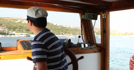 kaptan : Young male skipper hands on a steering wheel of a boat motoring in mediterranean Sea at summer time