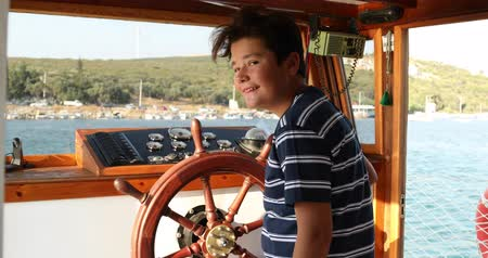 Young male skipper hands on a steering wheel of a boat motoring in mediterranean Sea