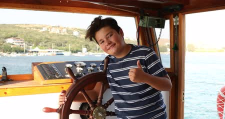 voyager : Young male skipper hands on a steering wheel of a boat motoring in mediterranean Sea