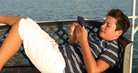 Happy teenager gaming with smart phone on yacht deck at summer vacation Dostupné videozáznamy