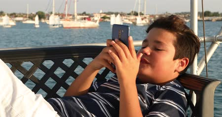 Portrait of a caucasian teenager playing video game with smartphone on yacht at sunny summer day