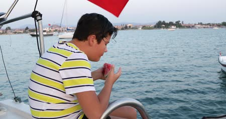 voyager : Portrait of a happy preteen school child on boat trip eating watermelon on a sunny summer day