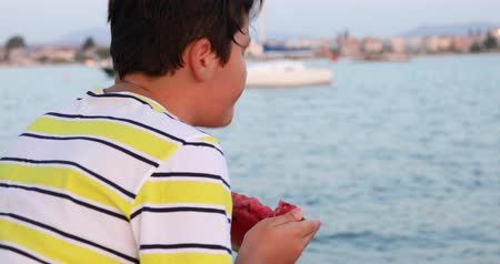 melão : Portrait of a happy preteen school child on boat trip eating watermelon on a sunny summer day