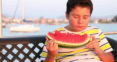 Portrait of a happy preteen school child on boat trip eating watermelon on a sunny summer day