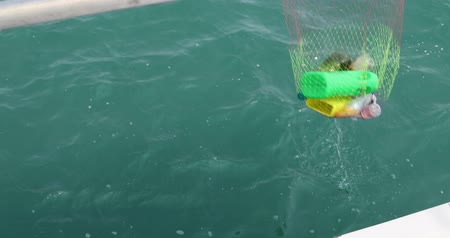 waste water : Volunteer collecting plastic garbages on sea with landing net