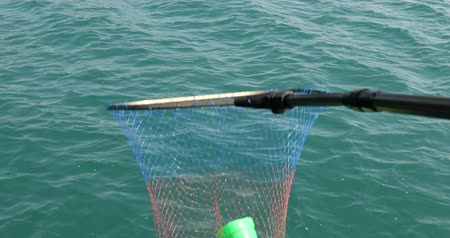 coletando : Volunteer collecting plastic garbages on sea with landing net