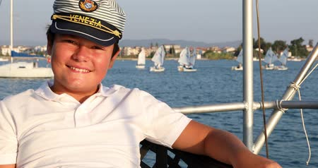 Portrait of a cute teenage boy sitting on the boat deck looking at the camera, smiling and posing