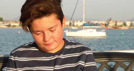 voyager : Portrait of a one young boy relaxing on the yacht deck at summer holiday. Travel people summer concept