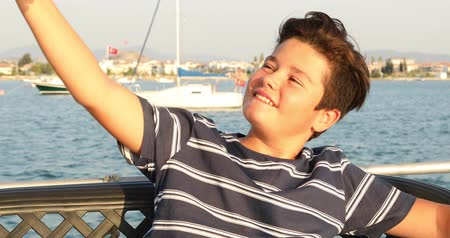 Portrait of a teenager boy on yacht deck taking selfie from smart phone at summer vacation. Travel, holiday, people, technology concept