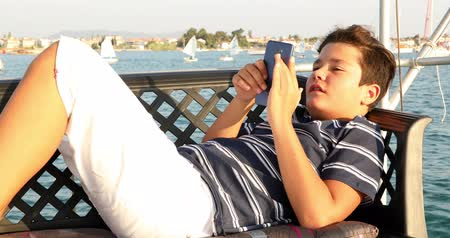 Portrait of a caucasian teenager traveling by yacht and playing video game with smartphone at sunny summer vacation day