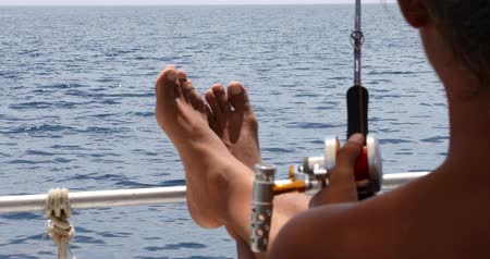 catch : Business man on yacht deck with fishing rod relaxing under the summer sun at summer holiday. People vacation nature travel leisure and summer concept