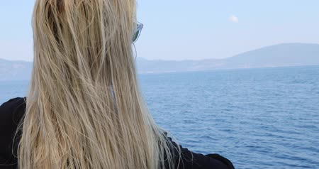 voyager : Portrait of a caucasian female tourist woman with blond hair  in glasses  on luxury sailing boat relaxing and looking around at summer vacation. Summer travel and vacation people concept