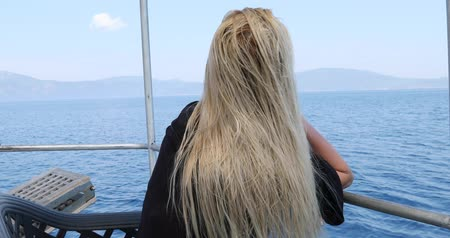 voyager : Portrait of a caucasian female tourist woman with blond hair  in glasses  on luxury sailing boat relaxing and looking around at summer vacation. Summer travel sea  vacation and people concept Stock Footage