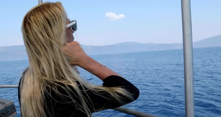 voyager : Portrait of a caucasian female tourist woman in glasses  on luxury sailing boat relaxing and looking around at summer vacation. Summer travel and vacation people concept Stock Footage