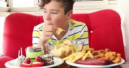 engorda : Portrait ofa caucasian teenage boy sitting at home and eating unhealthy foods. Stock Footage