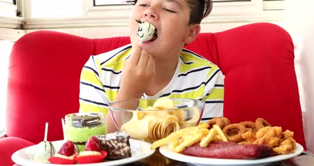 karbonhidratlar : Portrait ofa caucasian teenage boy sitting at home and eating unhealthy foods. Stok Video