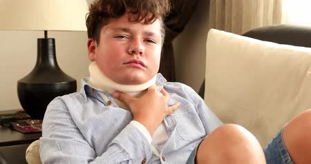zayıf : Portrait of a poor young boy with a neck brace looking in the camera
