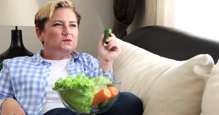 tartás : Portrait of a caucasian middle aged woman sitting on sofa and eating low calorie food. Diet. Dieting concept. Healthy Food.