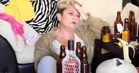 intimidated : Middle aged miserable woman in depression, drinking alcohol Stock Footage