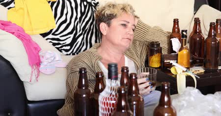 contemplative : Middle aged miserable woman in depression, drinking alcohol Stock Footage