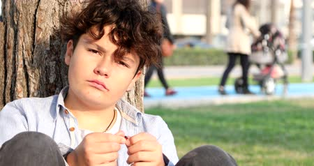 durulması : Portrait of a one teenage boy sitting at the city park and looking at the camera seriously