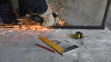 locksmith : Specialist at work, cut metal with a electric angle grinder. Along the lying working tools: pencil, tape measure and try square Stock Footage