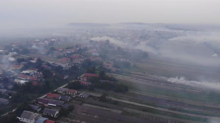 devastated : Village is in the smoke, atmospheric pollution, burning weeds on the field. Autumn time, Ukraine. Aerial view from drone, fly forward in a straight line Stock Footage