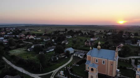 lugar : Ancient Christian temple and bell tower near, swallows fly in the sky, sunset. Aerial view of Ukrainian village