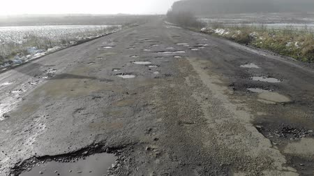 onarılmış : Destroyed road, difficult traffic area, threat of traffic accident. Countryside, Ukraine Stok Video