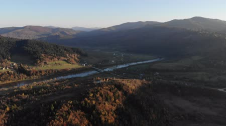 карпатская : Aerial view of nature in Carpathians, Ukraine. Autumn landscape with mountains, forests and river. Cozy wooden country house on the slopes of the mountain. Smooth fly forward