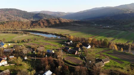 Aerial view of old village Lastivka in Carpathians, Ukraine. Autumn time, sunset, and beautiful landscape. Drone 4K