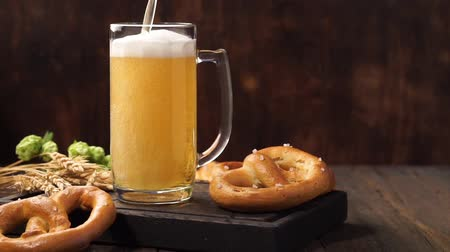 craft beer : Lager beer is pouring into a mug. Light beer on a wooden table. Stock Footage