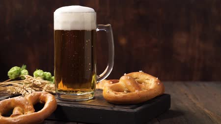 pretzel : Fresh foamy Lager beer in a glass mug on a dark wooden table.